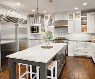 Beautiful Kitchen in Luxury Home with Island, Hardwood Floors, and Stainless Steel Refrigerator